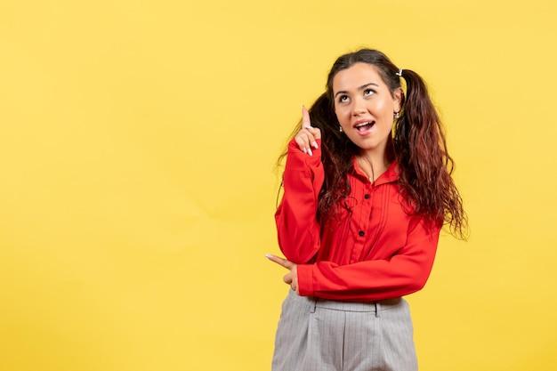 Vue de face jeune fille en chemisier rouge avec des cheveux mignons pointant sur fond jaune couleur enfant enfant fille jeunesse innocence