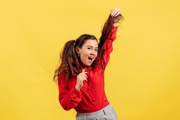 Vue de face jeune fille en chemisier rouge avec des cheveux mignons posant sur fond jaune enfant fille jeunesse innocence couleur enfant