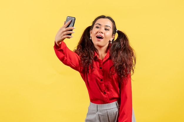 Vue de face jeune fille en chemisier rouge avec des cheveux mignons prenant selfie sur fond jaune enfant fille jeunesse innocence enfant couleur