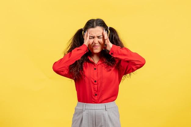 Vue de face jeune fille en chemisier rouge avec des cheveux mignons souffrant de maux de tête sur fond jaune couleur enfant enfant fille jeunesse innocence