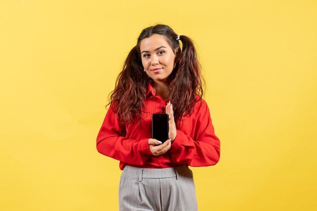 Vue de face jeune fille en chemisier rouge avec des cheveux mignons tenant un téléphone sur un bureau jaune enfant fille jeunesse innocence couleur enfant