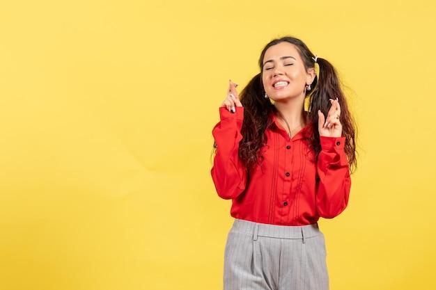 Vue de face jeune fille en chemisier rouge avec des cheveux mignons et un visage heureux sur fond jaune innocence enfant fille jeunesse couleur enfant