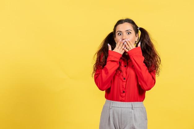Vue de face jeune fille en chemisier rouge avec des cheveux mignons et un visage surpris sur fond jaune innocence enfant fille jeunesse couleur enfant