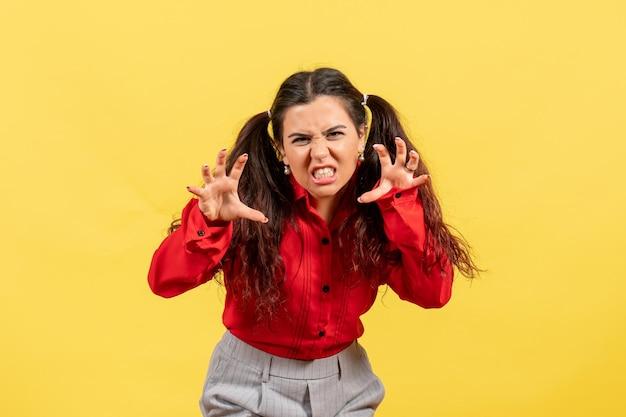 Vue de face jeune fille en chemisier rouge avec un visage effrayant sur fond jaune enfant enfant fille femme jeunesse sentiment d'émotion
