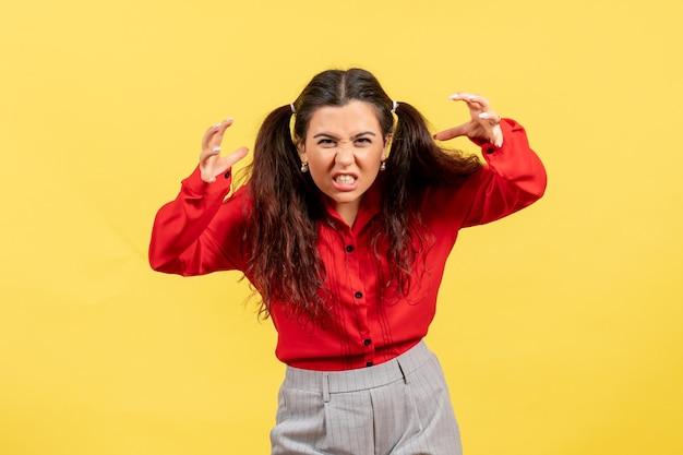 Vue de face jeune fille en chemisier rouge avec un visage effrayant sur fond jaune sentiment féminin enfant fille jeunesse émotion