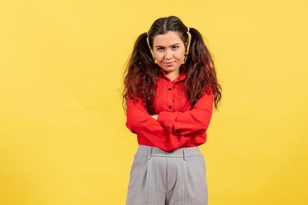 Vue de face jeune fille en chemisier rouge avec un visage fou sur fond jaune sentiment féminin enfant fille jeunesse émotion