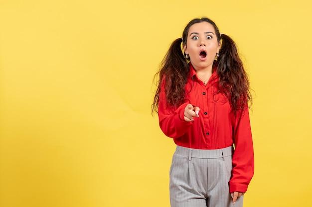 Vue de face jeune fille en chemisier rouge avec visage surpris sur fond jaune couleur innocence enfant fille jeunesse kid