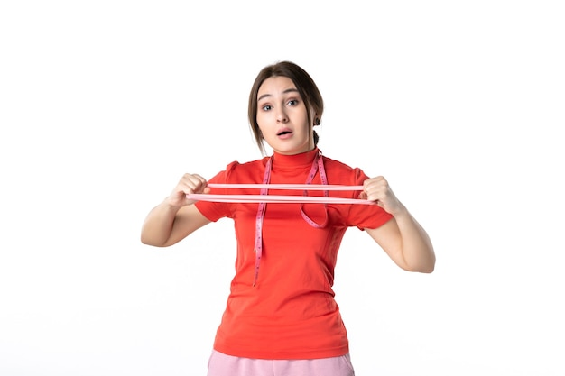 Vue de face d'une jeune fille confuse en chemisier rouge-orange étirant l'accessoire élastique sur fond blanc