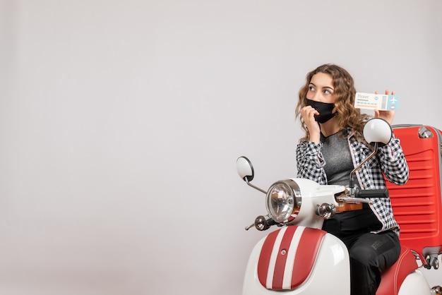 Vue de face de la jeune fille confuse avec masque sur cyclomoteur tenant un billet de voyage
