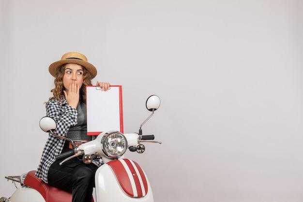Vue de face jeune fille sur cyclomoteur brandissant le presse-papiers