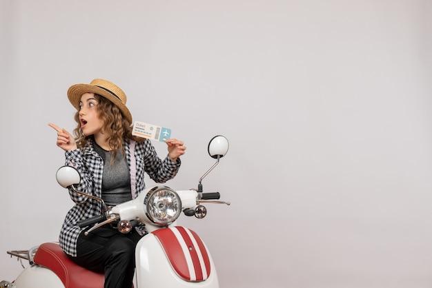 Vue de face jeune fille sur cyclomoteur brandissant un ticket pointant vers la gauche