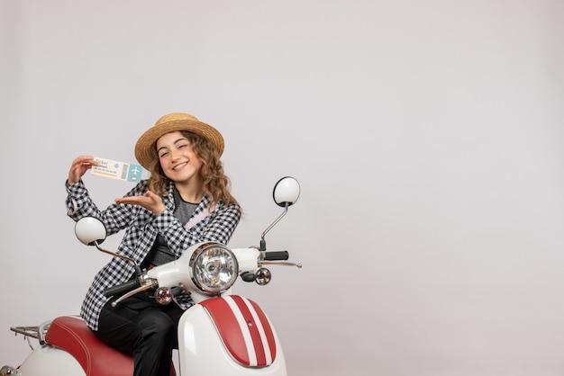 Vue de face jeune fille sur cyclomoteur brandissant un ticket