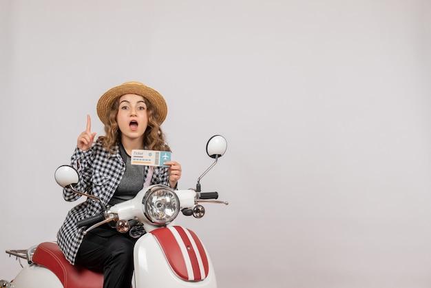 Vue de face jeune fille sur cyclomoteur holding ticket doigt pointé vers le haut