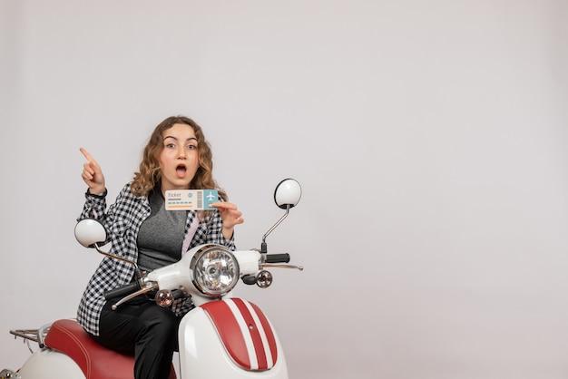 Vue de face jeune fille sur cyclomoteur holding ticket pointant vers la gauche