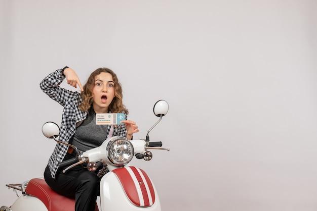Vue de face jeune fille sur cyclomoteur pointant sur son billet