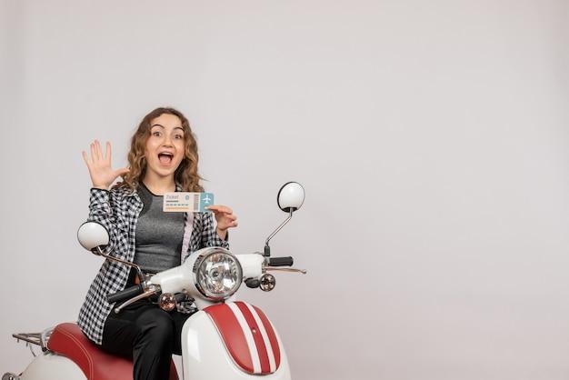 Vue de face de la jeune fille sur un cyclomoteur tenant un billet en agitant la main sur un mur gris