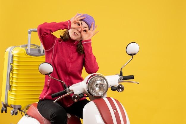 Vue de face jeune fille sur un cyclomoteur tenant des signes ok devant ses yeux