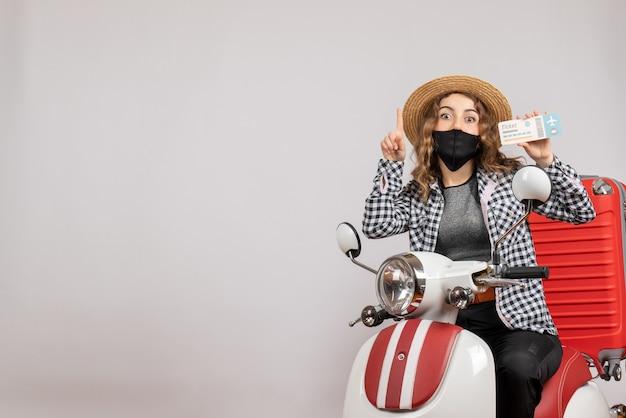 Vue de face jeune fille sur cyclomoteur avec valise tenant un billet