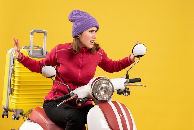 Vue de face jeune fille en difficulté sur un cyclomoteur