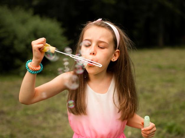 Vue de face de la jeune fille faisant des bulles de savon