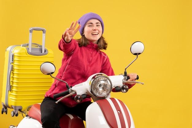 Vue de face jeune fille heureuse sur un cyclomoteur montrant trois doigts