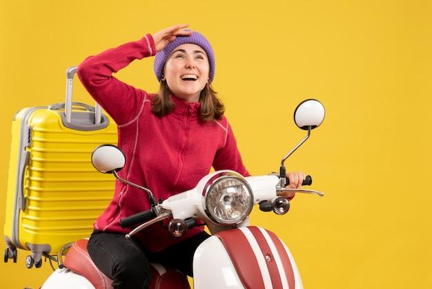 Vue de face jeune fille heureuse sur un cyclomoteur regardant quelque chose