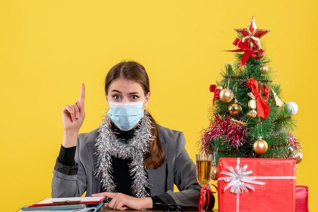 Vue de face jeune fille avec masque médical assis à la table montrant quelque chose avec arbre de noël doigt et cocktails cadeaux