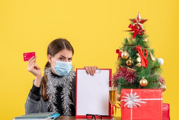 Vue de face jeune fille avec masque médical assis à la table tenant la carte de crédit noël arbre et cadeaux cocktail