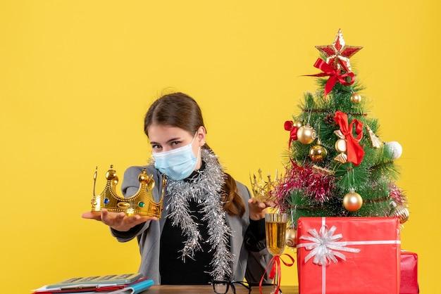 Vue de face jeune fille avec masque médical montrant arbre de noël de la couronne et cocktail de cadeaux