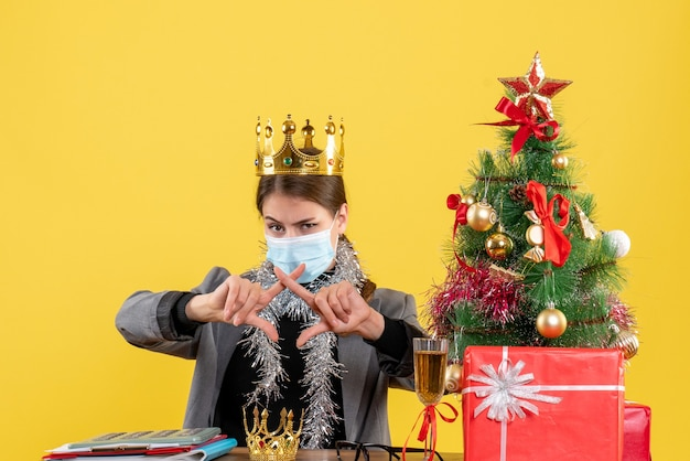 Vue de face jeune fille avec masque médical portant couronne croisant ses doigts arbre de noël et cadeaux cocktail