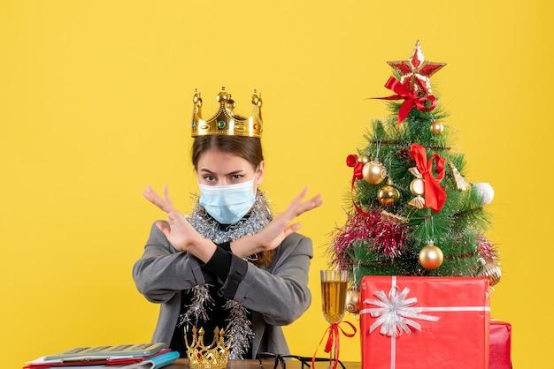 Vue de face jeune fille avec masque médical portant couronne croisant ses mains arbre de noël et cadeaux cocktail