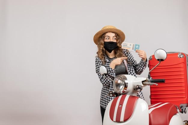 Vue de face jeune fille avec masque noir tenant un billet pointant vers la droite près d'un cyclomoteur rouge