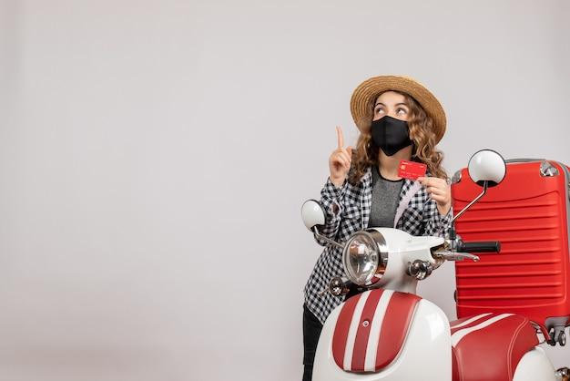 Vue de face jeune fille avec masque noir tenant un billet pointant vers le haut, debout près d'un cyclomoteur rouge