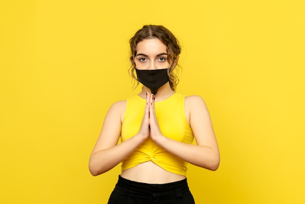Vue de face de la jeune fille priant sur le mur jaune