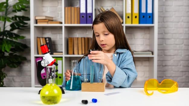 Vue de face de la jeune fille avec des tubes à essai et microscope