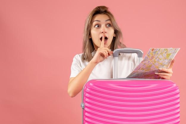 Vue de face jeune fille avec une valise rose tenant une carte faisant signe de silence