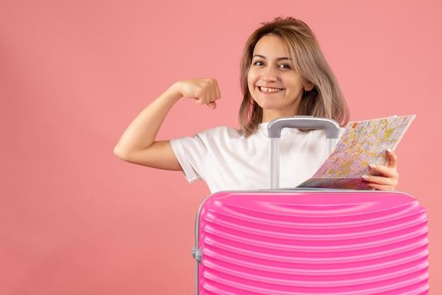 Vue de face jeune fille avec une valise rose tenant une carte montrant le muscle du bras