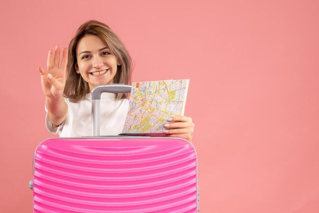 Vue de face jeune fille avec une valise rose tenant une carte montrant quatre doigts