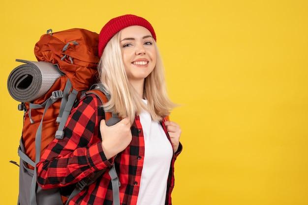 Vue de face jeune fille de voyage avec son sac à dos debout sur un mur jaune