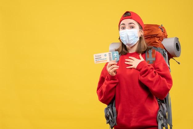Vue de face jeune fille de voyageur avec sac à dos et masque tenant un billet mettant la main sur sa poitrine