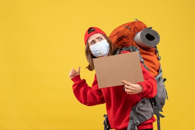 Vue de face jeune fille de voyageur avec sac à dos et masque tenant le carton pointant vers l'arrière