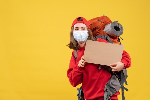 Vue de face jeune fille de voyageur avec sac à dos et masque tenant carton