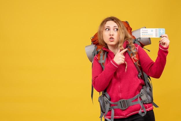 Vue de face de jeune fille voyageuse choquée dans un masque médical tenant et pointant un billet