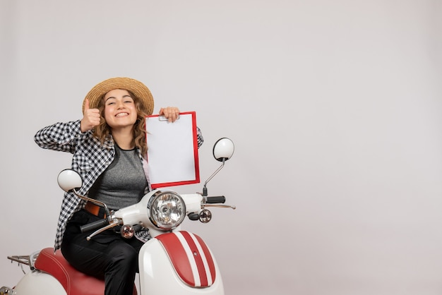 Vue de face jeune fille voyageuse sur cyclomoteur tenant un presse-papiers rouge donnant le pouce