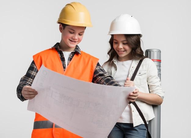 Vue de face jeune garçon et fille lisant le plan de construction