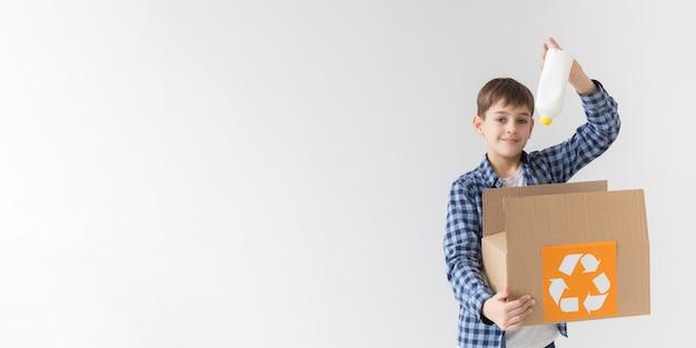 Vue de face jeune garçon heureux de recycler avec espace copie