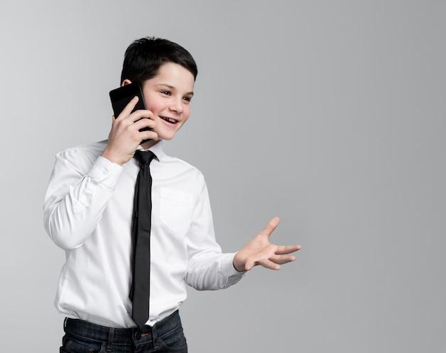 Vue de face jeune garçon parlant sur téléphone mobile