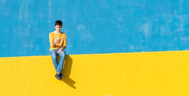 Vue de face d'un jeune garçon portant des vêtements décontractés, assis sur une clôture jaune contre un mur bleu tout en utilisant un smartphone