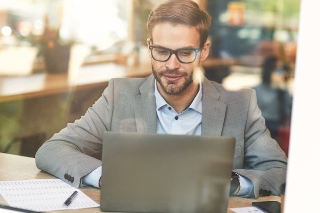 Vue de face d'un jeune homme d'affaires caucasien occupé ou d'un pigiste utilisant un ordinateur portable tout en travaillant