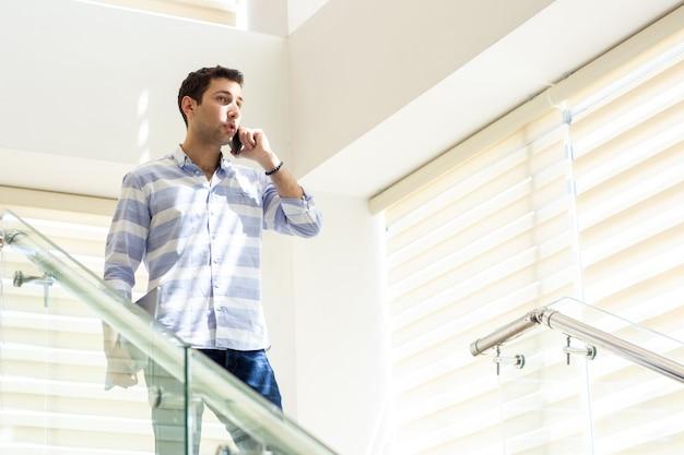 Une vue de face jeune homme d'affaires en chemise rayée parler et discuter des problèmes de travail au téléphone pendant la journée